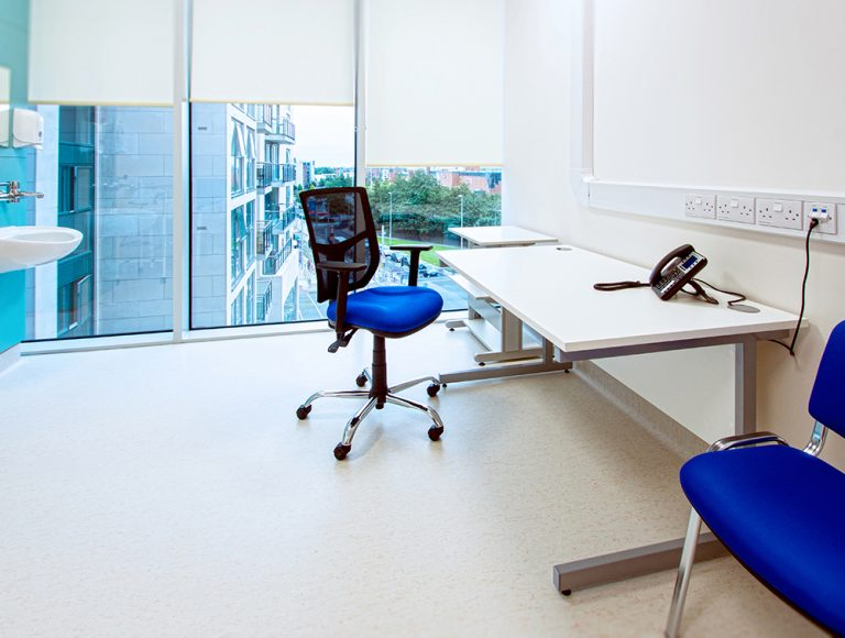 Bright blue chairs and cantilever desk in office with windows