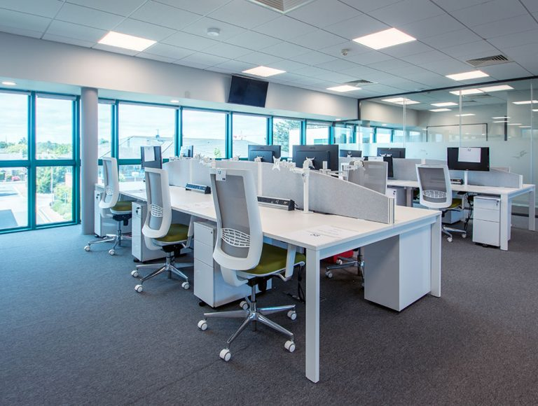 White workstations with monitor arms and white office chairs with pedestals