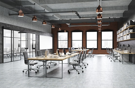 A large office space with desks and chairs under the spot lights