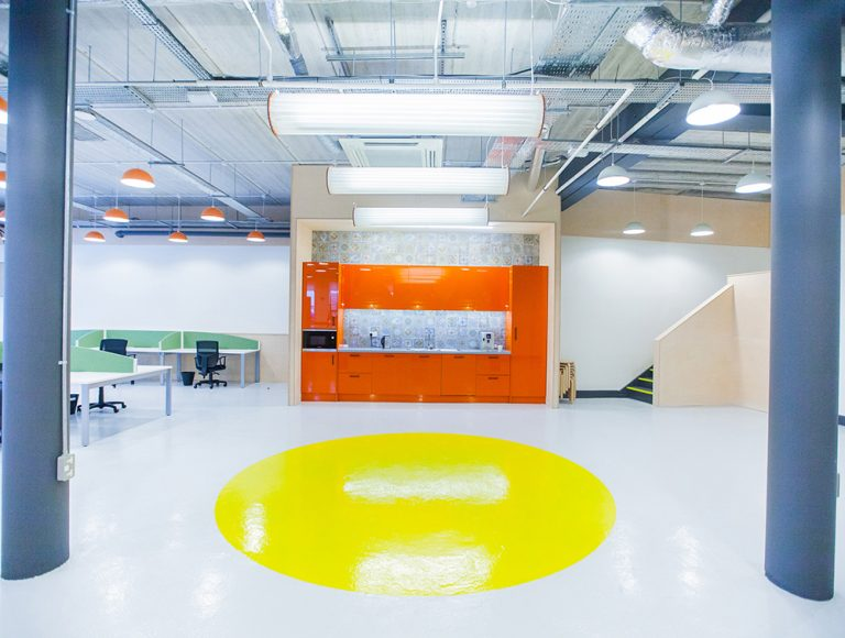 Open area with orange kitchenette and yellow circle on floor