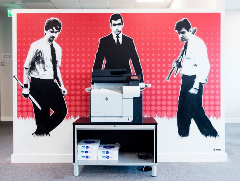 A photocopier in office in front of coloured mural stile plastered wall