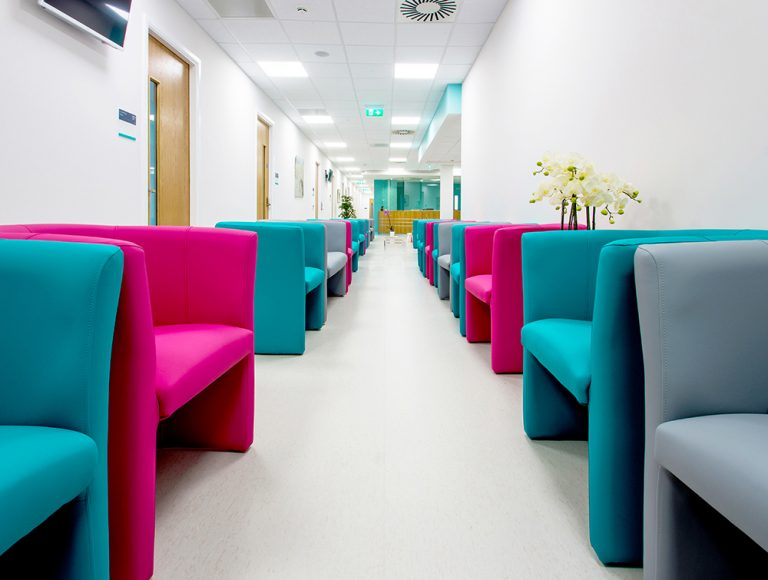 Row of vibrant armchairs down a grey corridor