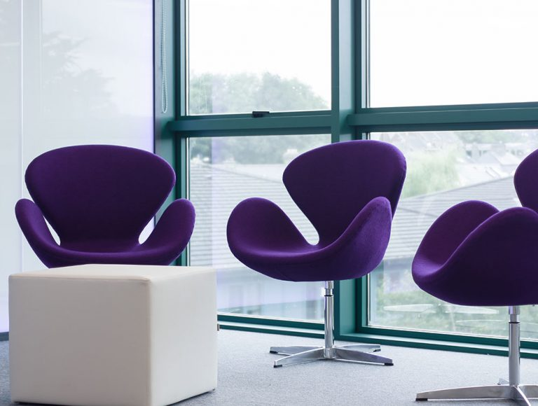 Three purple petal chairs with metal legs next to a large window