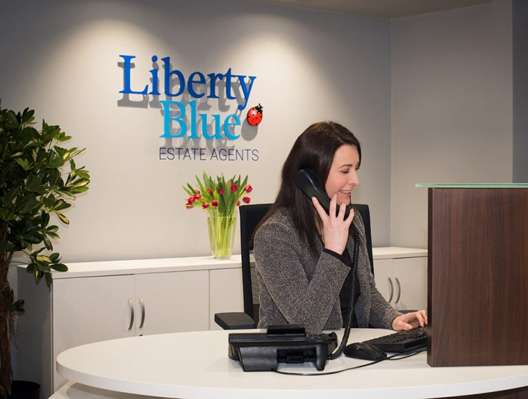 Woman in grey talking on phone while back of liberty blue logo
