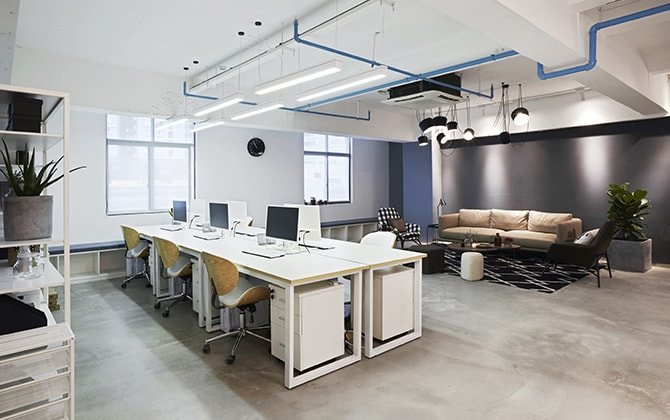 Open floor with white office furniture and a sofa